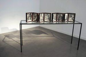 Collage #85. 2014. (Frente). Pareja de biombos de 4 hojas, collage, papel, hilo, bisagras, mesa de hierro y vidrio. 27,5 x 84 cm cada biombo (abierto), mesa 90 x 185 x 50 cm. Vista general.